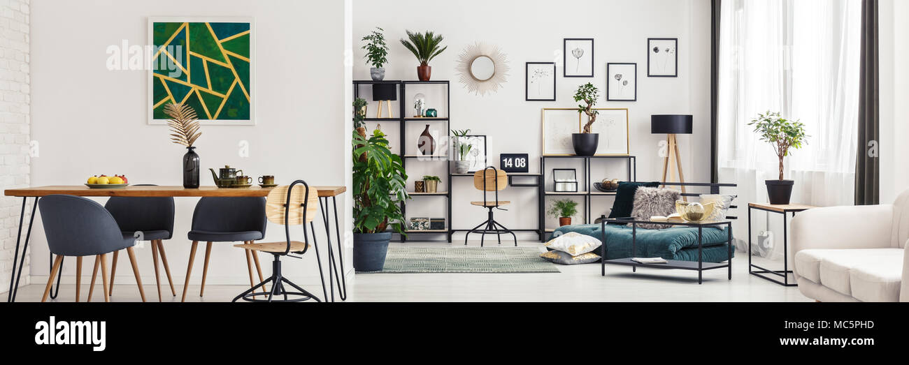 Bright, open space flat interior with dining table, geometric poster and fresh plants in home office - Stock Image