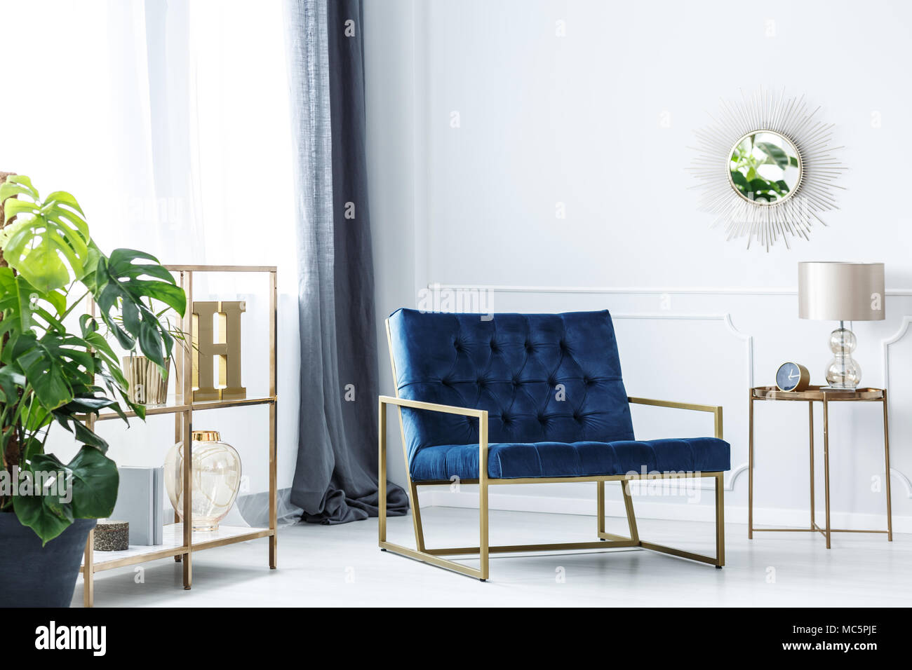 Navy blue chair standing in white room interior with golden ...