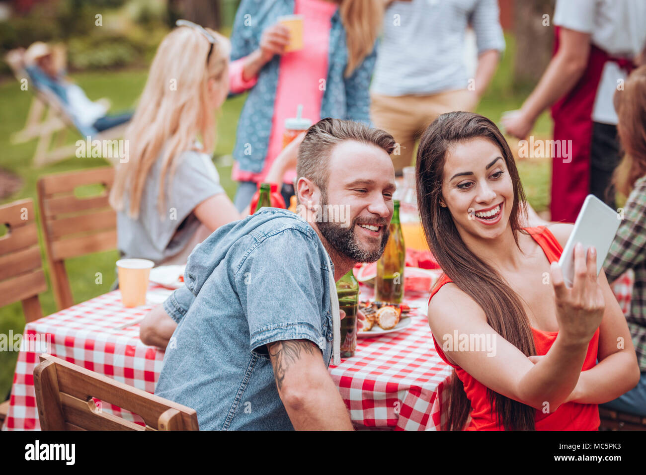 Smiling woman taking photo with a friend during a birthday party in the garden - Stock Image