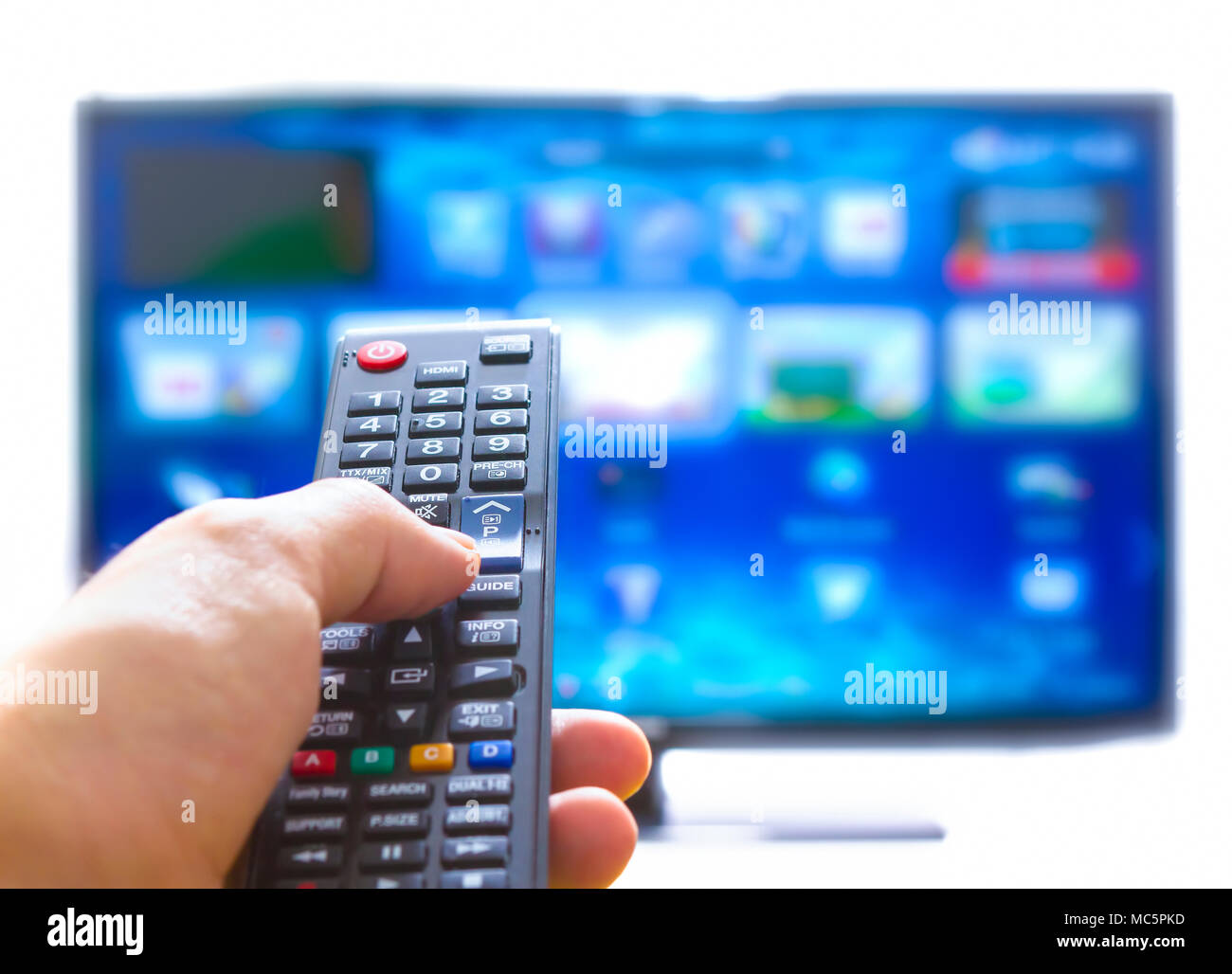 Hand pressing on remote control and changes channels thumb