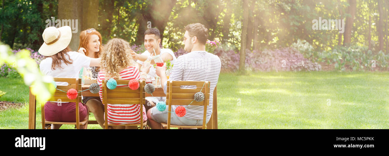 Panorama of happy friends eating lunch in the garden during a birthday party - Stock Image