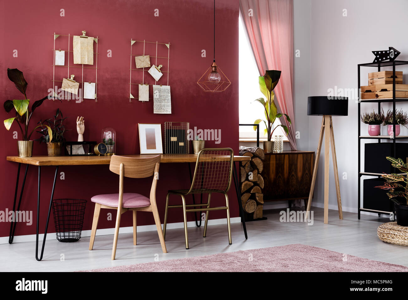 Plant and wooden lamp in dark red home office interior with chair at desk with poster - Stock Image