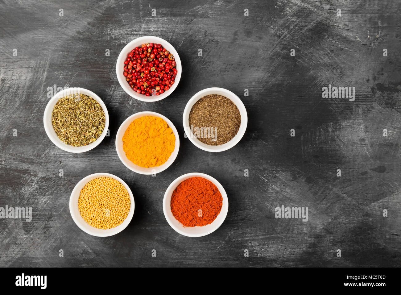 Various spices in bowls on black background. Top view, copy space. Food background - Stock Image