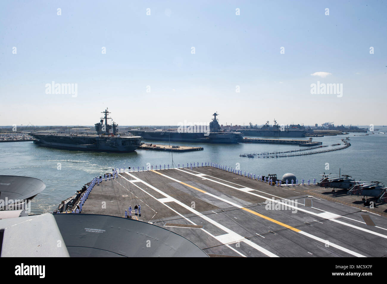 180411-N-UJ486-438  NORFOLK (April 11, 2018) Sailors man the rails aboard the aircraft carrier USS Harry S. Truman (CVN 75) during the ship's departure from homeport. Harry S. Truman is underway as the flagship for the Harry S. Truman Carrier Strike Group which includes; the guided-missile cruiser USS Normandy (CG 60), and the guided-missile destroyers USS Arleigh Burke (DDG 51), USS Bulkeley (DDG 84), USS Farragut (DDG 99), USS Forrest Sherman (DDG 98), USS The Sullivans (DDG 68), USS Winston S. Churchill (DDG 81) for a scheduled deployment. (U.S. Navy photo by Mass Communication Specialist 3 Stock Photo