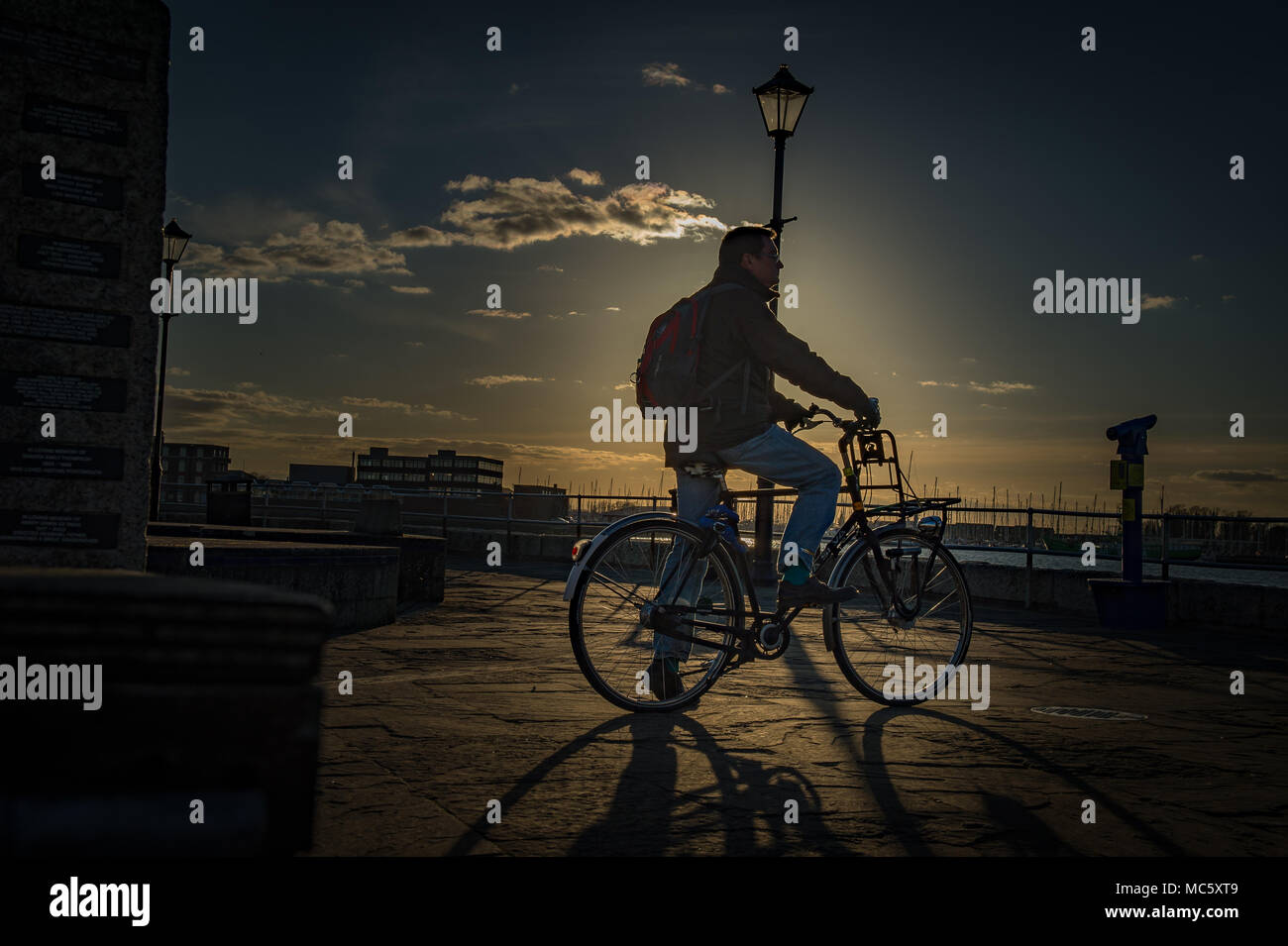 Silhouette of a Cyclist at Sunset in Old Portsmouth - Hampshire, UK Stock Photo