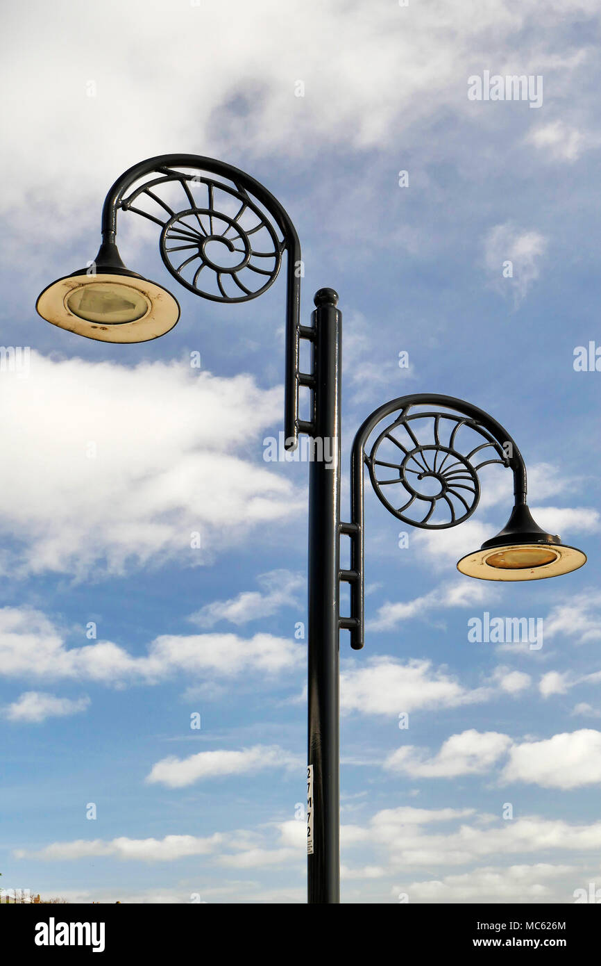 A typical street light in Lyme Regis with the characteristic ammonite design. - Stock Image