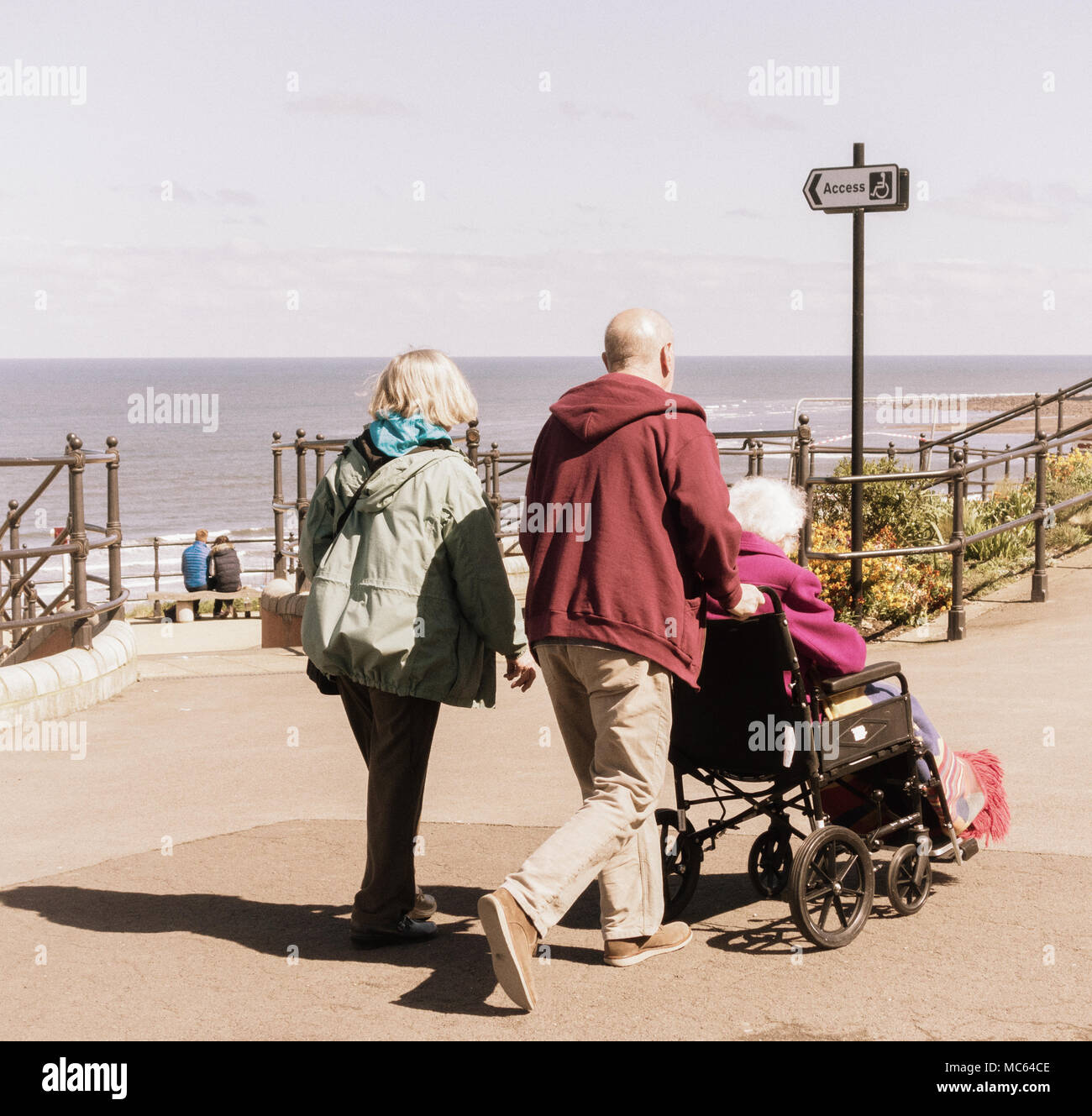Couple and elderly woman in wheelchair near beach uk. Caring for elderly parent/person... - Stock Image