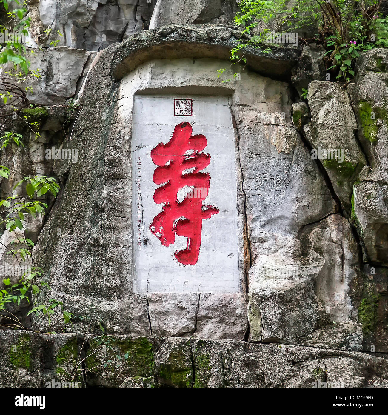 An inscription and stone carving at the base of Solitary Beauty Peak, Guilin, China. The red painted Chinese character is Shou, which means longevity. - Stock Image