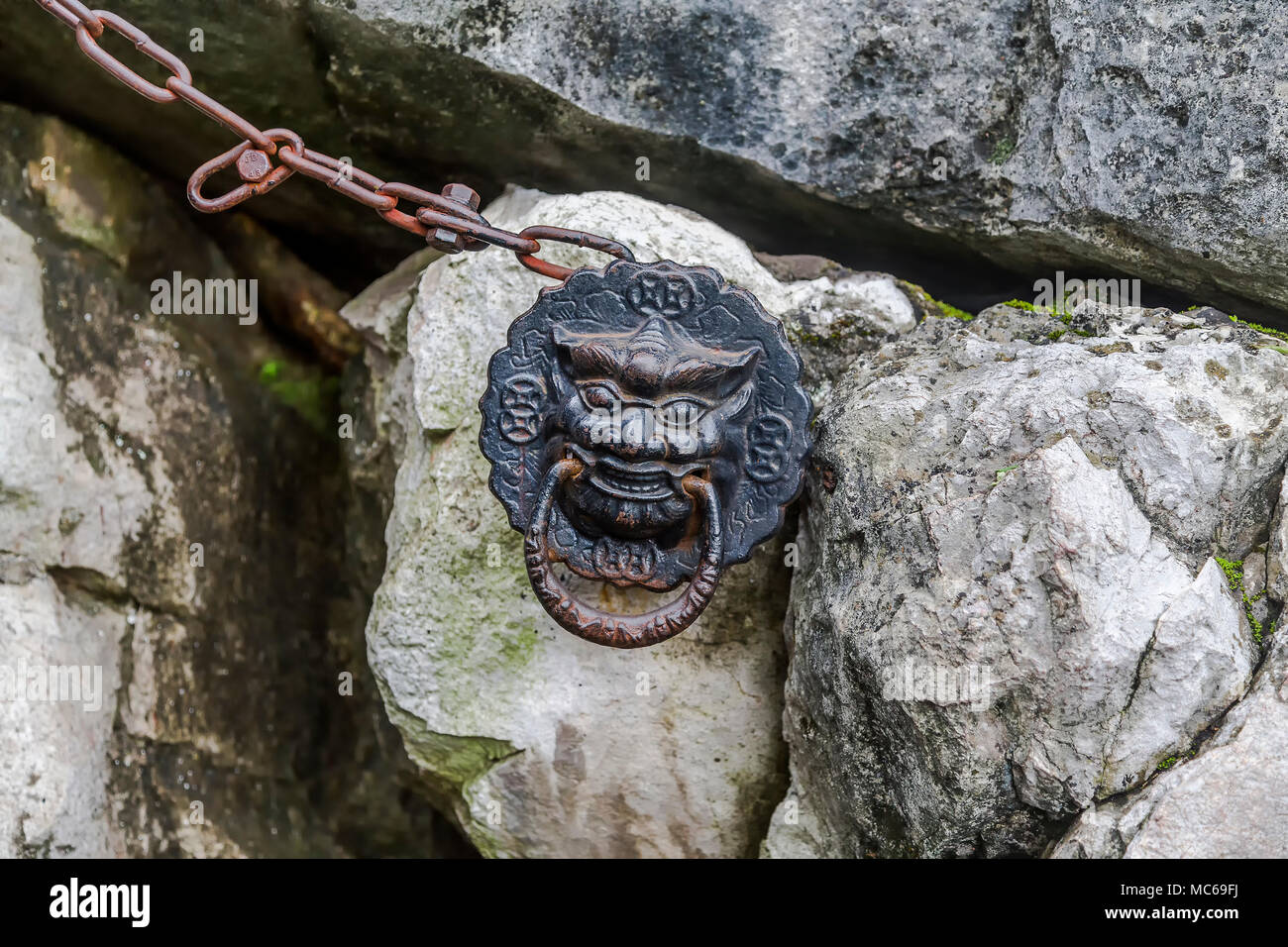 A traditional Chinese metal lion head is attached to a chain and the steep rock face of the Solitary Beauty Peak. Guilin, China. - Stock Image