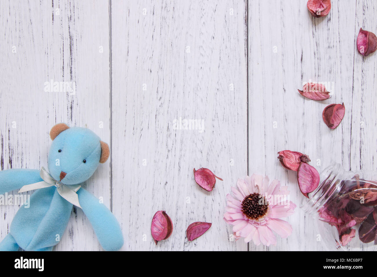 f5b4939aee0af Flat lay stock photography vintage white painted wood floor purple flower  petals and glass bottle blue bear doll