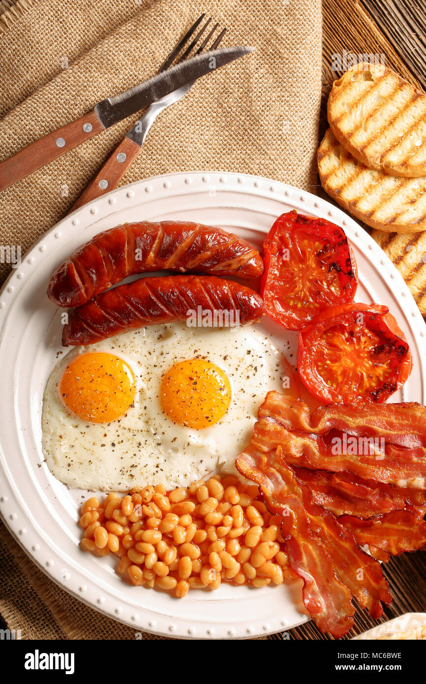 English Breakfast with sausages, grilled tomatoes, egg, bacon, beans and bread on white plate - Stock Image