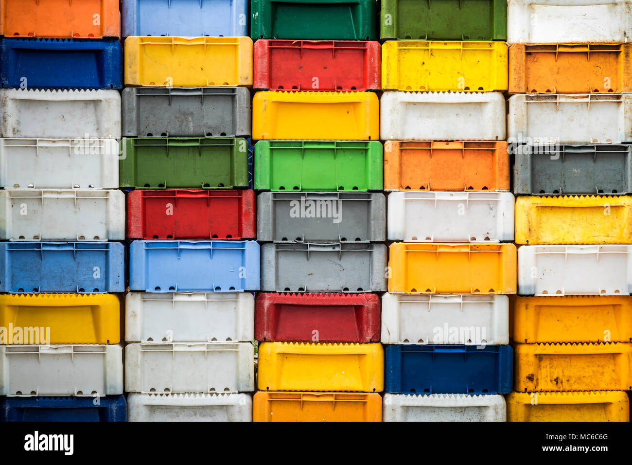 Stacked returnable boxes of fish in various colors. - Stock Image