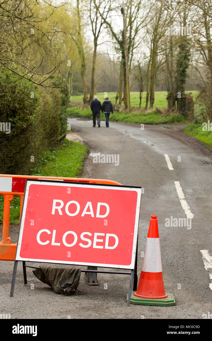 A road temporarily closed due to heavy rain that has made a river fording point unpassable further on from the two people walking. Dorset England  Uk - Stock Image
