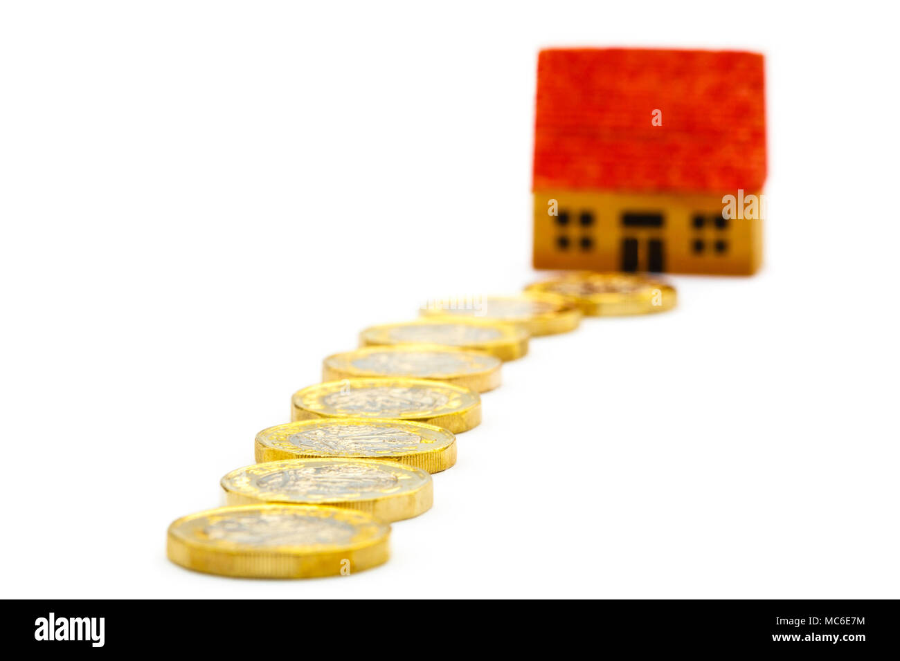 Path of money new pound £ coins pounds GBP leading to a house to illustrate property prices values and saving for a home ownership concept. UK Britain - Stock Image