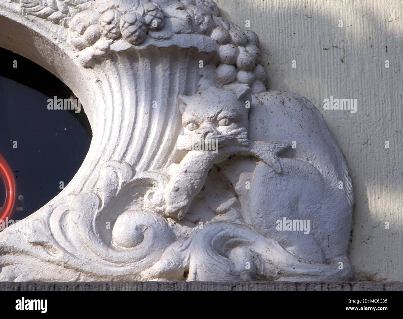 Animals cat with fish in its mouth relief carving above the