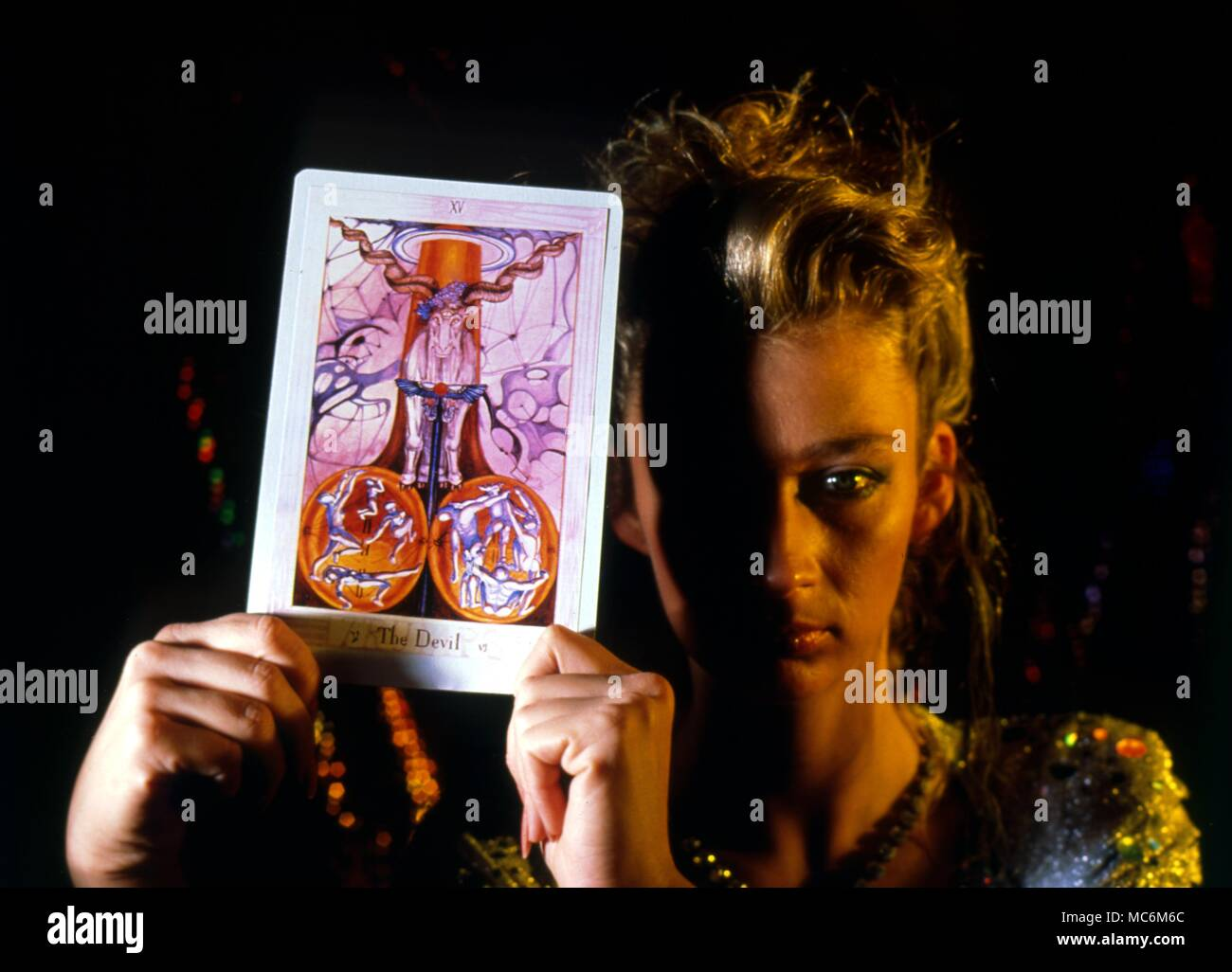 Tarot Cards Woman holding up the Tarot card, The Devil, from the