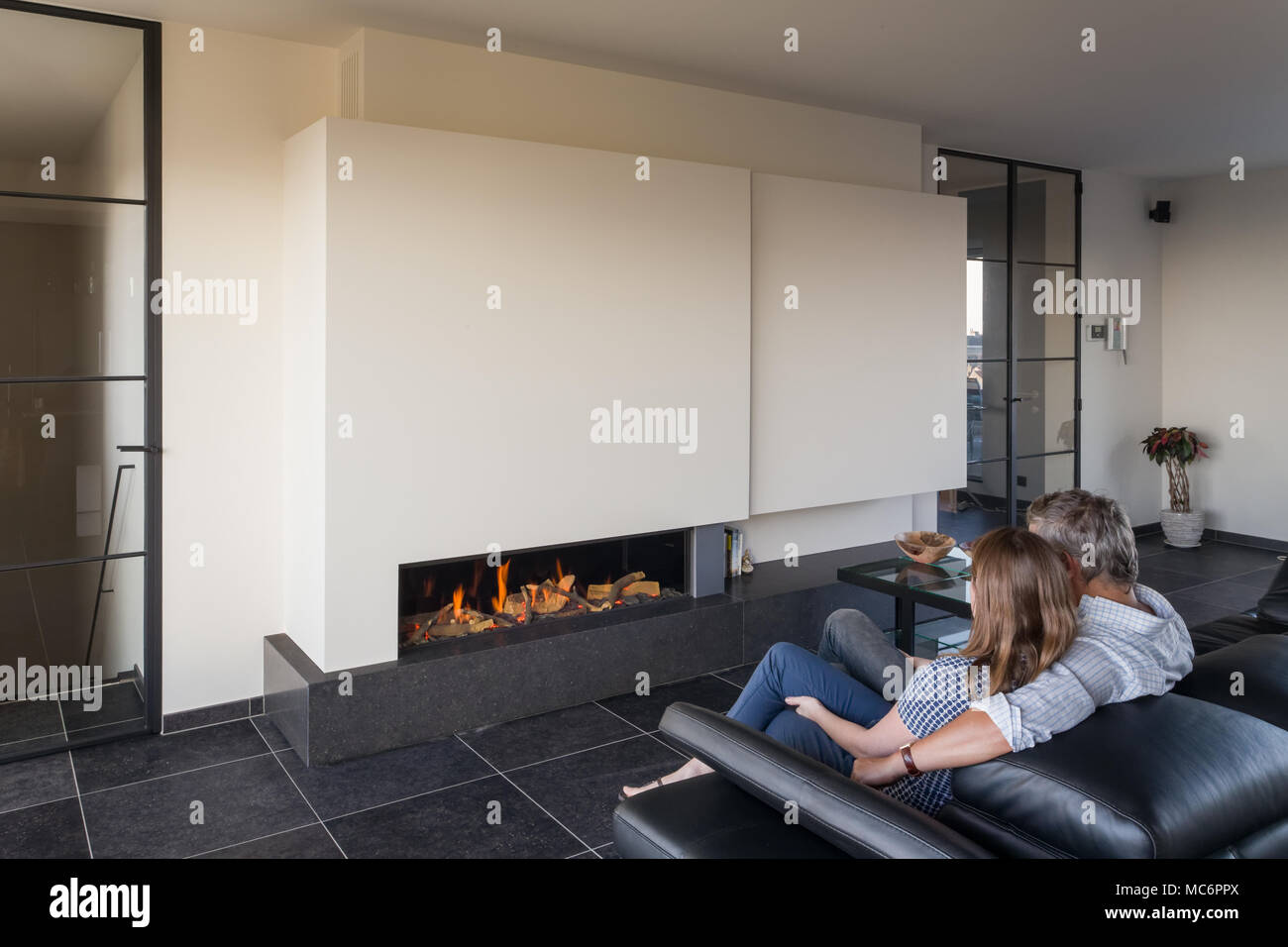 Couple sitting on sofa at home in front of modern fireplace - Stock Image