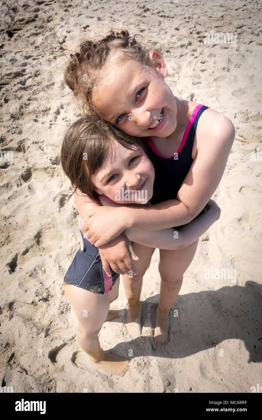 Portrait of a two smiling sisters hugging each other at the beach. Stock Photo