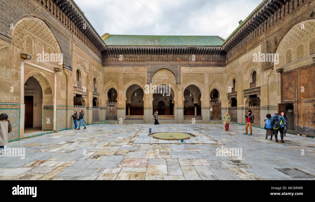 MOROCCO FES MEDINA BOU INANIA MADRASA BUILT BY MARINIDS MARBLE COURTYARD  LACERIA WOODWORK CEDAR BEAMS AND TILED ARCHED DOORWAYS - Stock Image