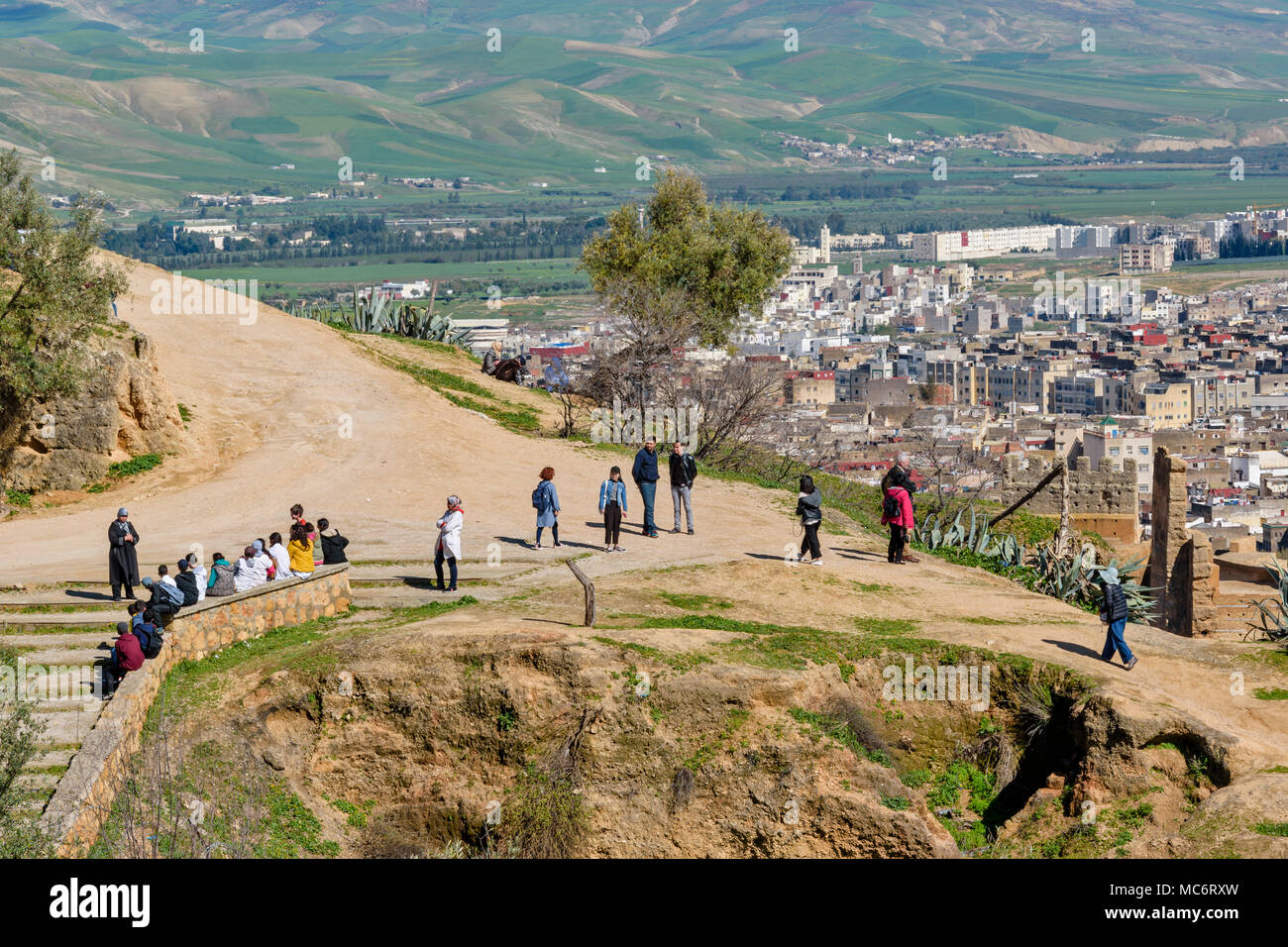 MOROCCO FES MEDINA OUTDOOR SCHOOL LESSON AND TOURISTS NEAR THE TOMB OF THE MERENIDS OVERLOOKING THE CITY - Stock Image