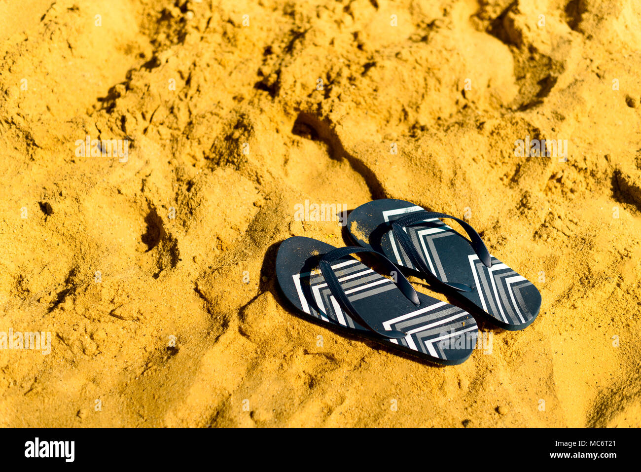 9b54651c6be0 Summer slippers. Navy blue flip flop on yellow sand beach background. Copy  space