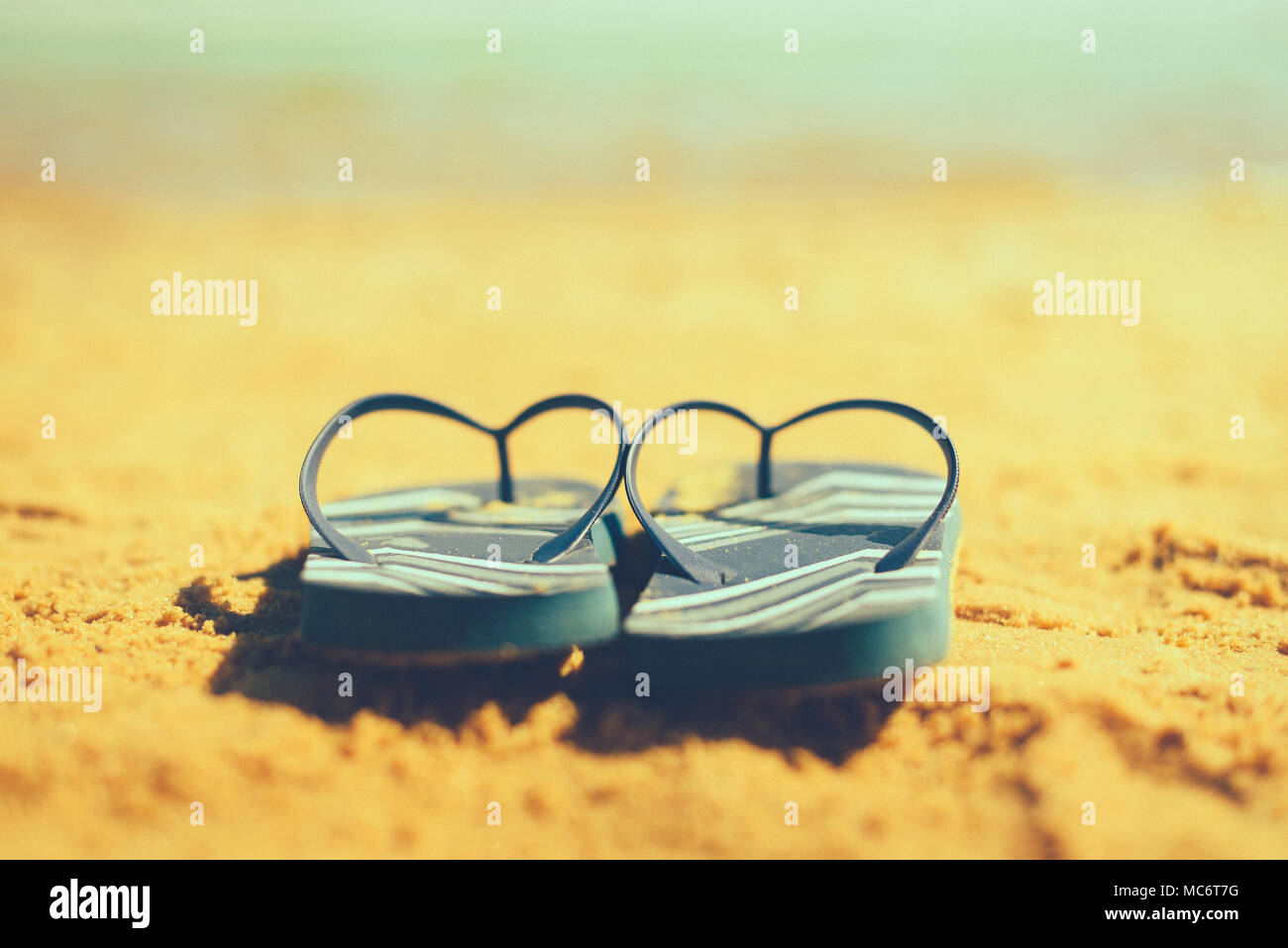 2d83d3f3ad2c Navy flip flop on yellow sand beach with blue sea and sky background. Copy  space. Summer