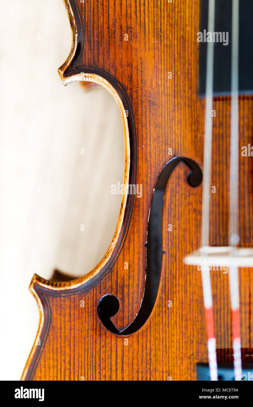 Focus on F hole in violin body belly. Top view, detaled macro with shalow depth of field on strings and bridge - Stock Image