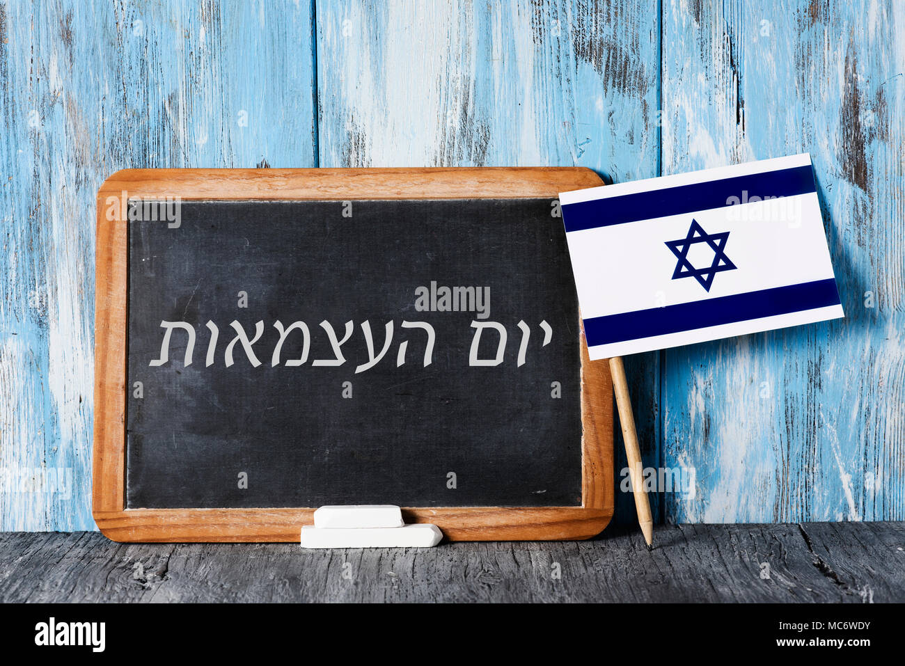 a wooden-framed chalkboard with the text independence day written in hebrew in it, some pieces of chalk and an israeli flag on a rustic wooden surface - Stock Image