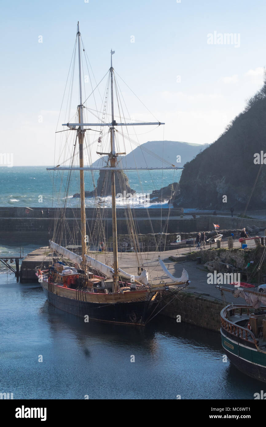 Poldark filming location of Charlestown - two masted old sailing ships in the harbour with rocks, sea and coast beyond Stock Photo