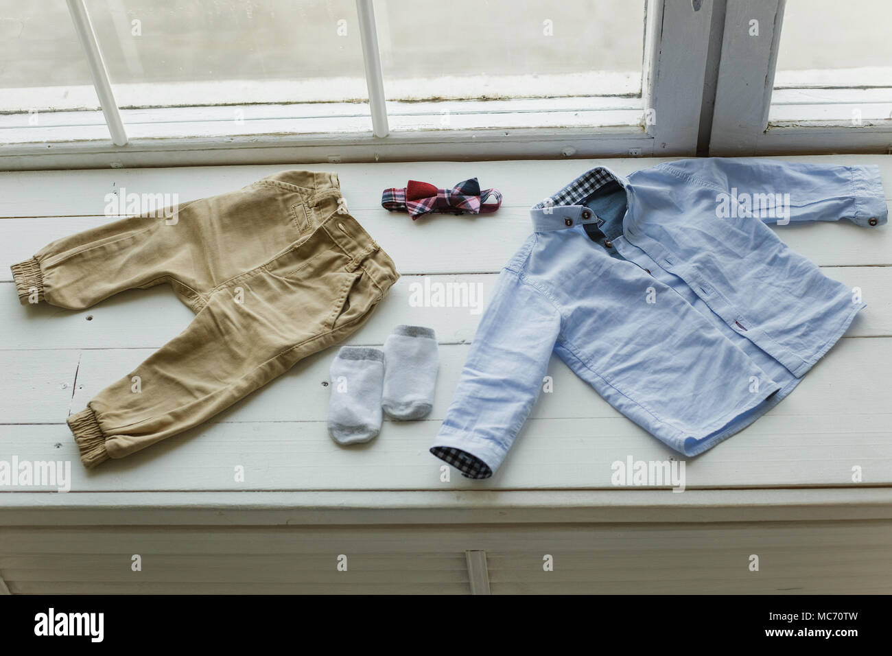 Set of baby clothes. Blue shirt, brown pants, white socks and red bowtie laying on white windowsill. Horizontal color photography. - Stock Image