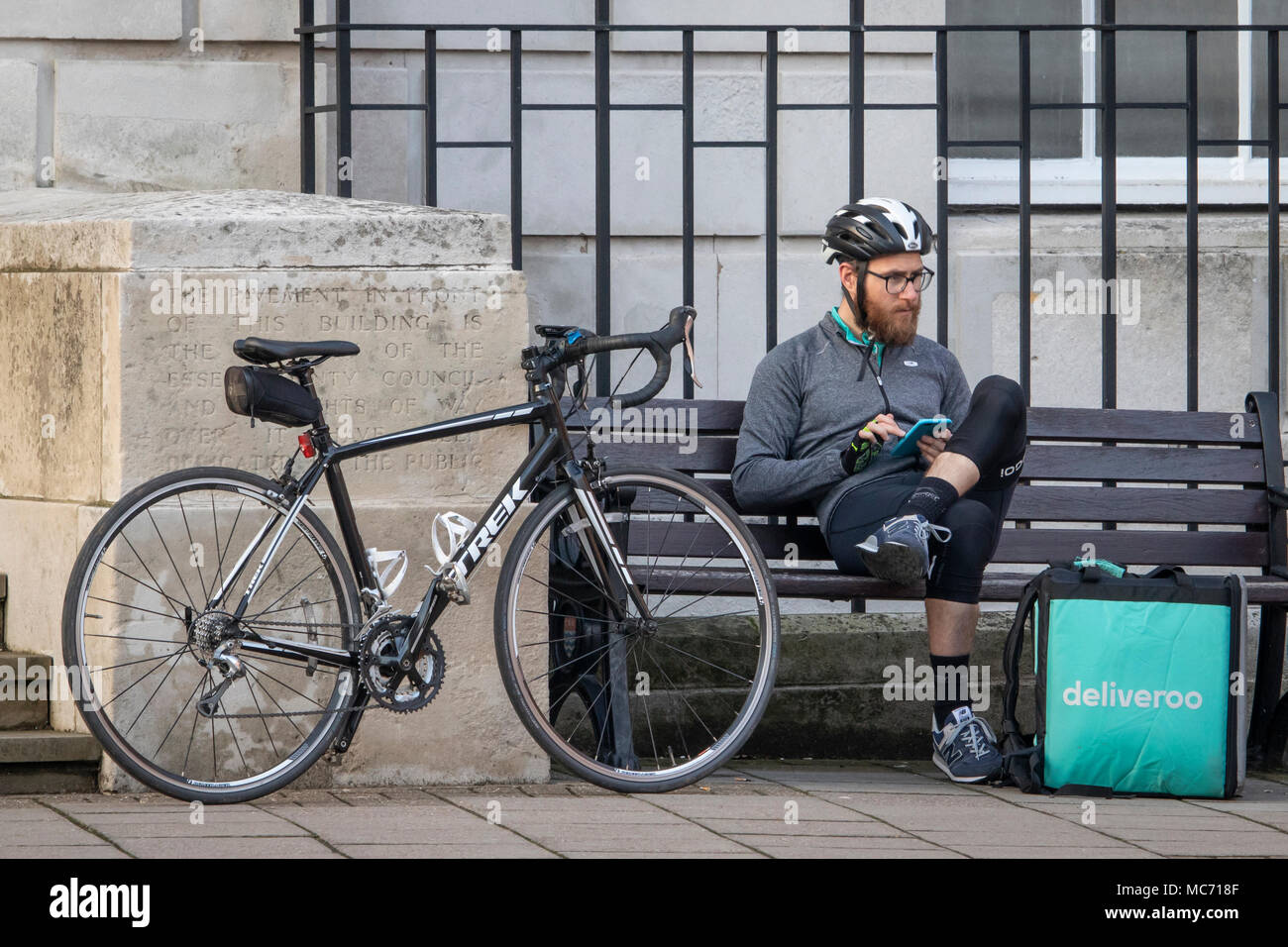 48c41340ca4 A deliveroo delivery cyclist of the gig economy with Trek Cycles bicycle  rests on a bench in Chelmesford town centre and uses a mobile phone