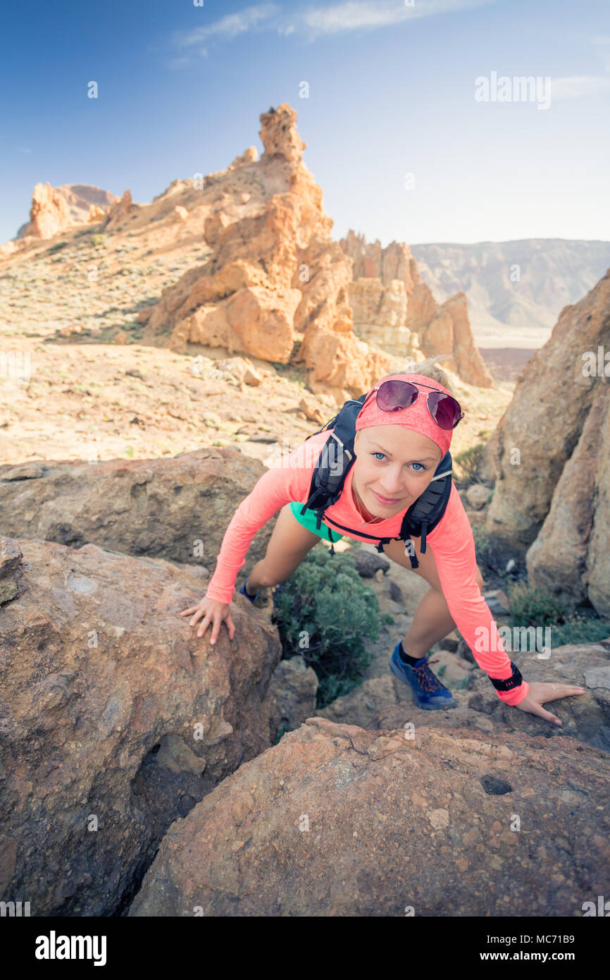 Woman hiker reached mountain top. Runner or climber walking and looking at inspirational landscape on rocky trail on Tenerife, Canary Islands Spain. F - Stock Image