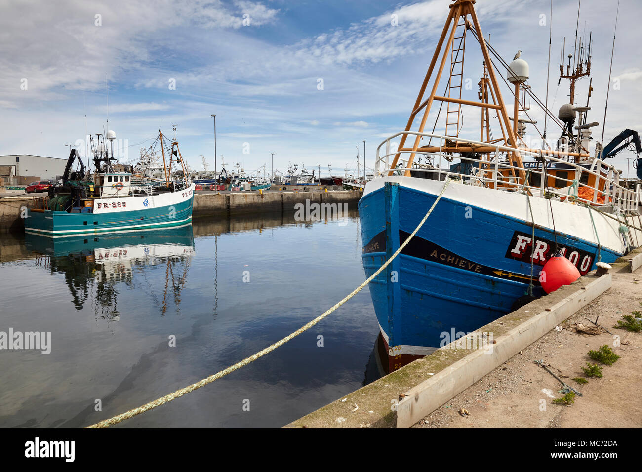 Moored at Fraserburgh Harbour, The ACHIEVE, FR 100, a near shore fishing vessel with EL-SHADDAI FR 285 moored in the background. - Stock Image