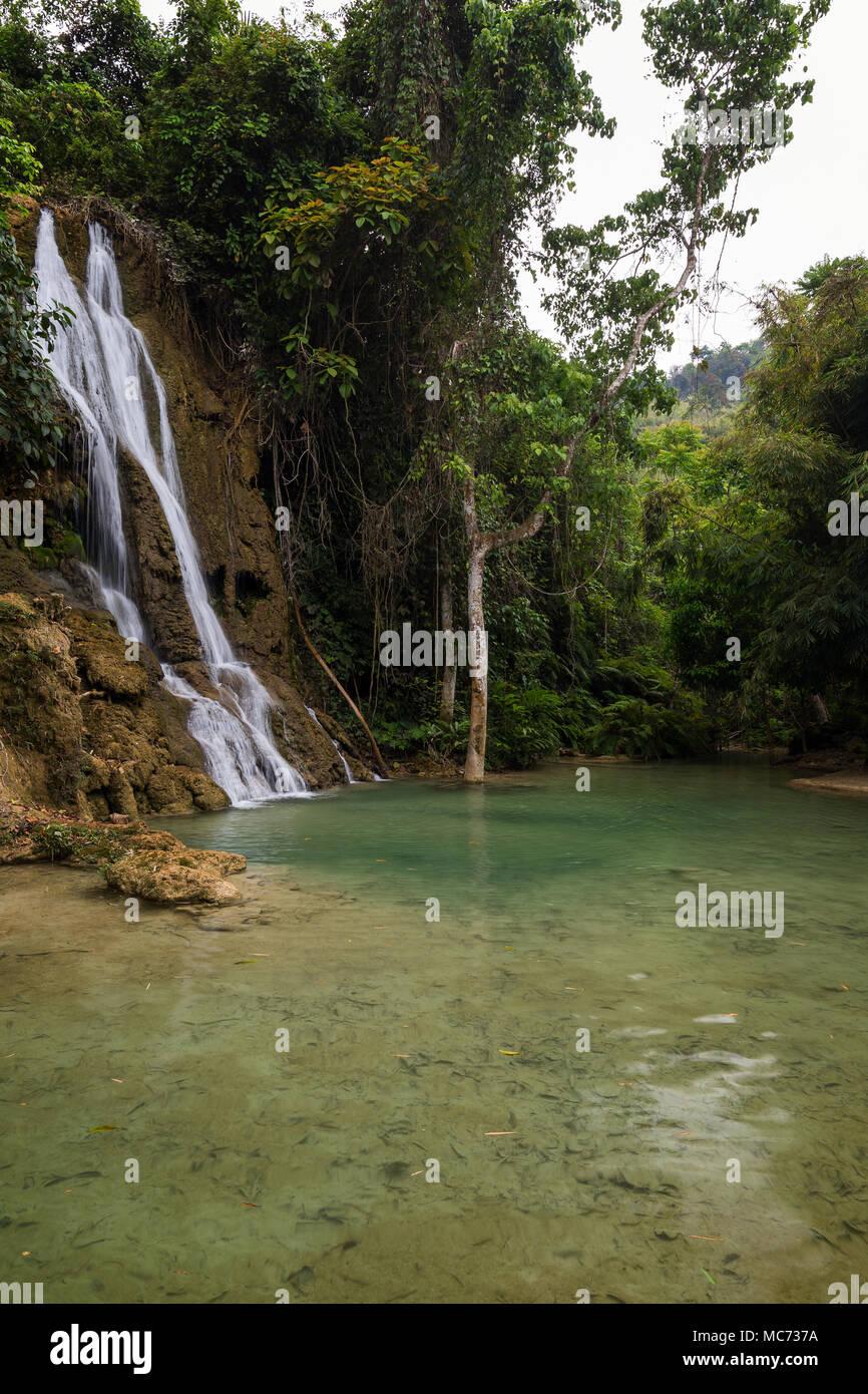 View of idyllic Khoun Moung Keo Waterfall, pond and lush trees near Luang Prabang in Laos. - Stock Image