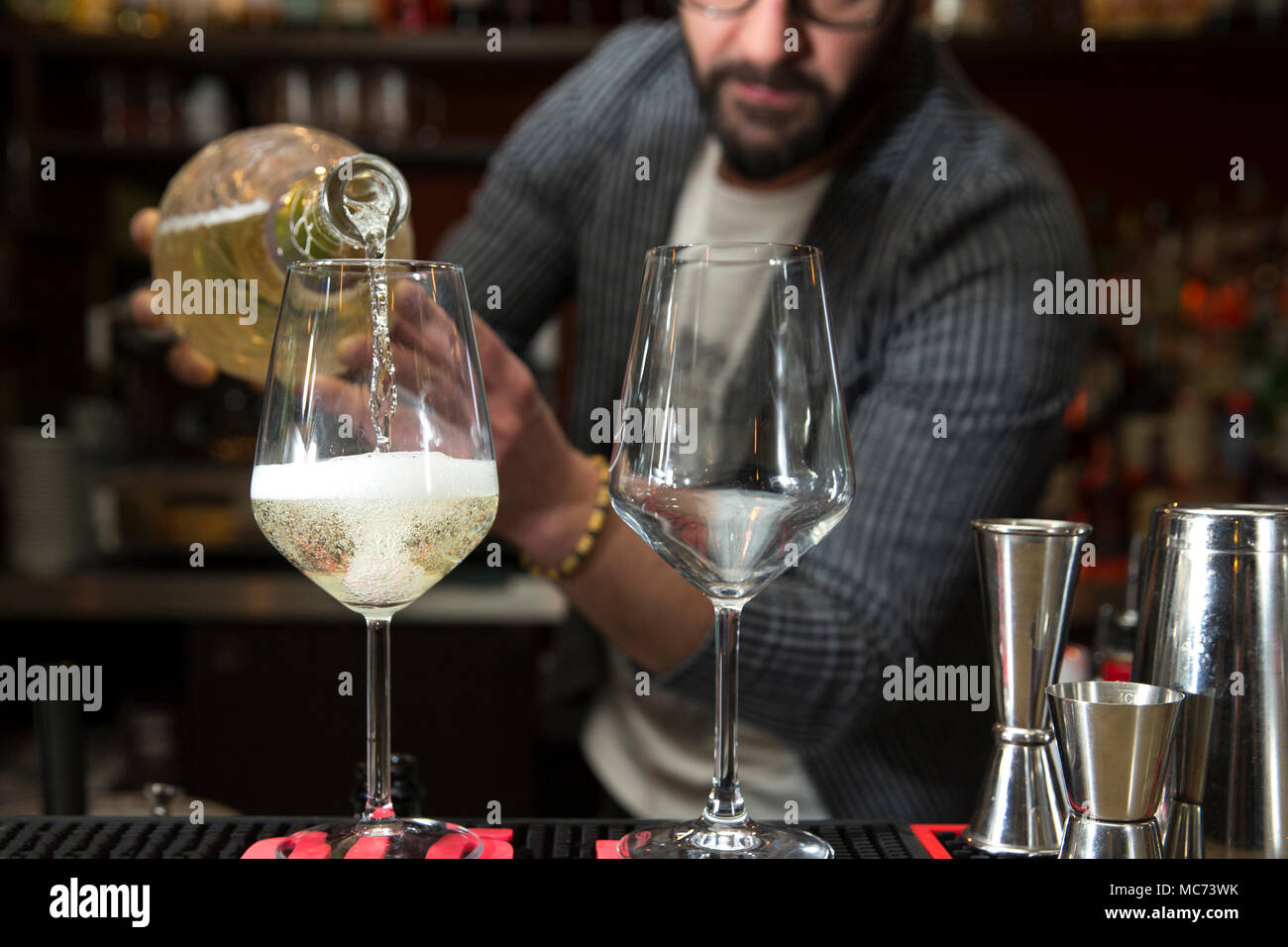 closeup of a barman working behind a bar counter, pouring prosecco in two wine glasses with focus on the glasses - Stock Image