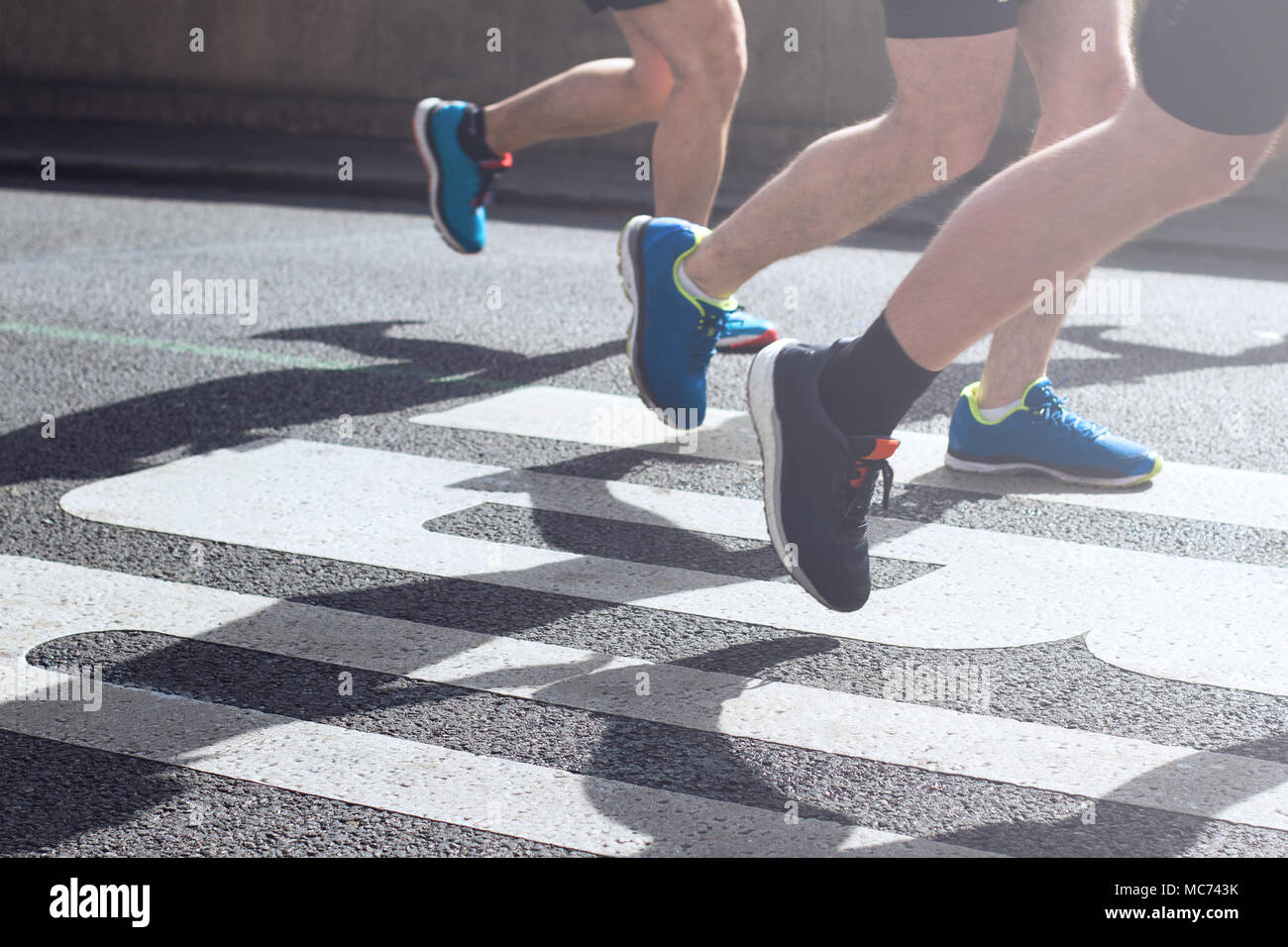 closeup view of synchronized marathon runners feet and legs with motion blur running in the light of the morning on city tarmac road - Stock Image