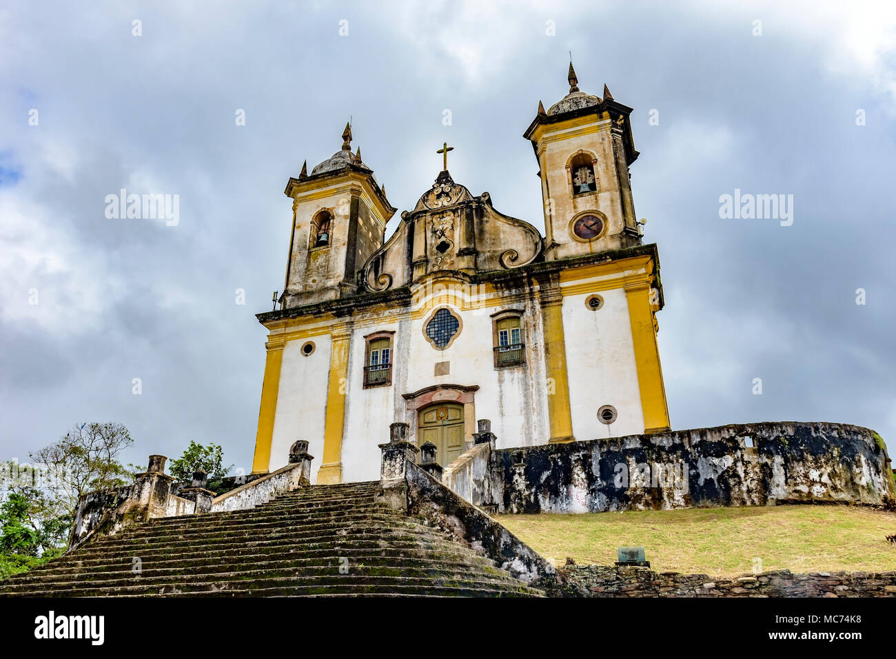 Ancient and aged historical church high in one of the several hills of the city of Ouro Preto with dark clouds in background - Stock Image
