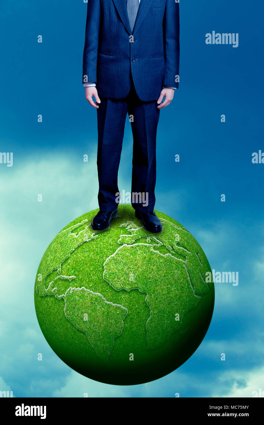 man standing on green earth, sustainable business and corporate social responsibility concept - Stock Image