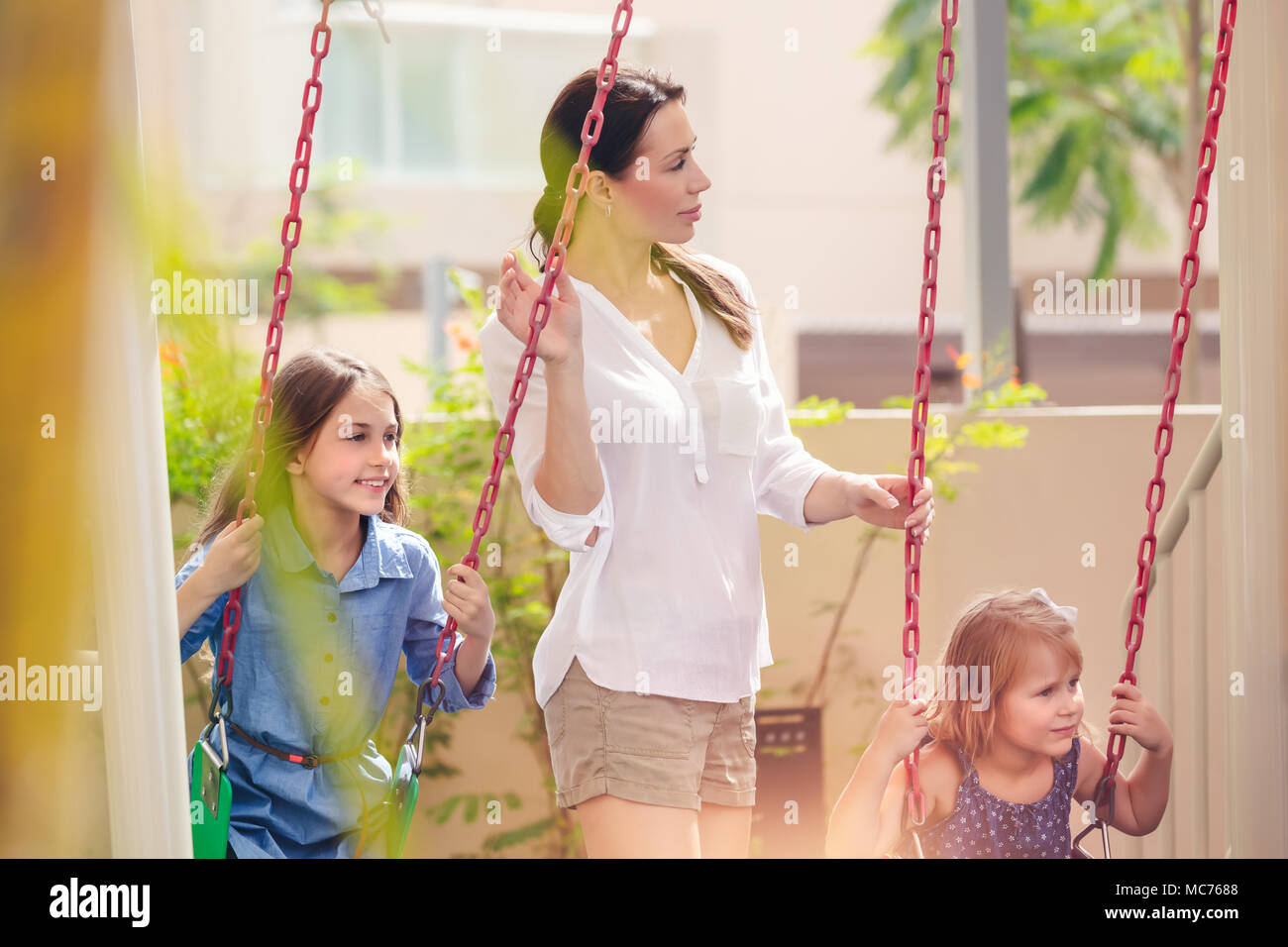 Mother with two daughters on playground, beautiful young mom rocks her precious girls on the swing, happy family spending weekend together - Stock Image