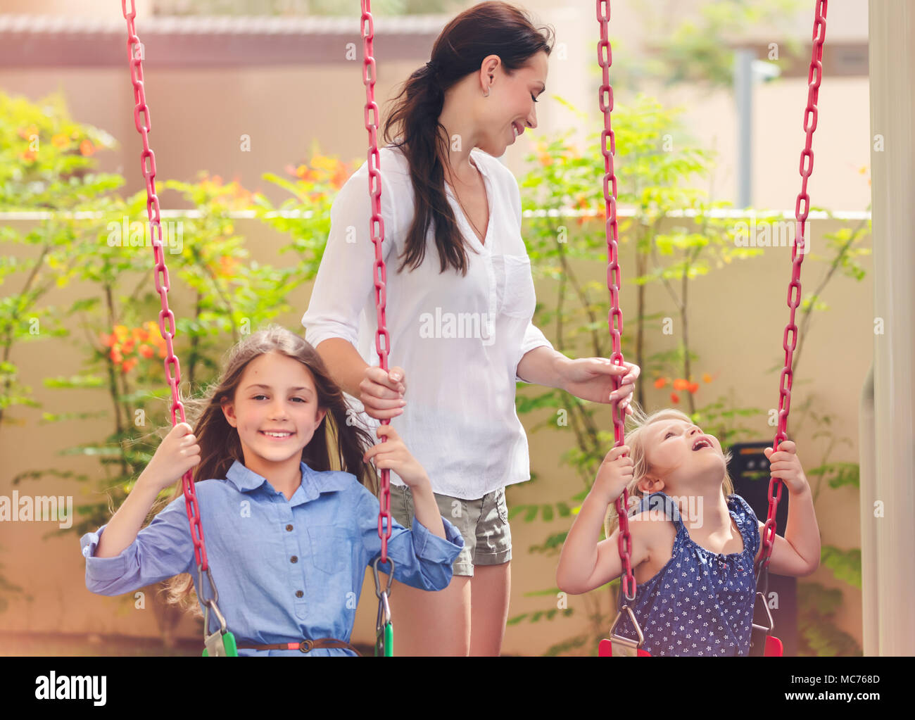 Mother with two daughters on a playground, beautiful young mom rocks her precious girls on the swing, amusement for outdoors kids, happy family spendi - Stock Image