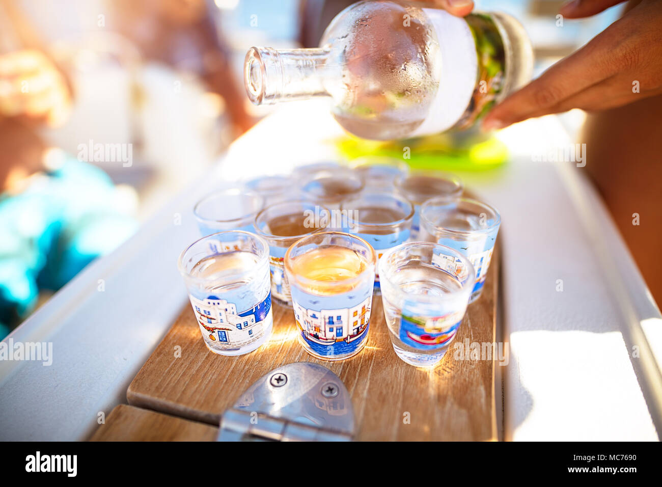 Party on the beach, refill glass with alcoholic beverage, drinking shots with friends, enjoying freedom, happy carefree summer vacation - Stock Image