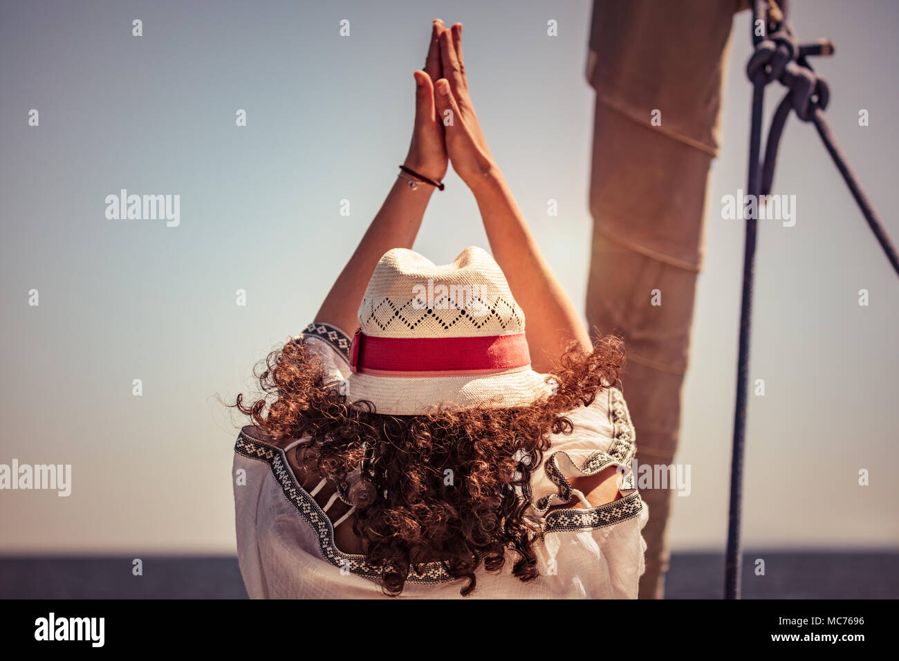 Woman doing yoga exercises, rear view of a female standing in yoga asana on the sailboat among sea, cleansing of aura, meditating on vacation - Stock Image