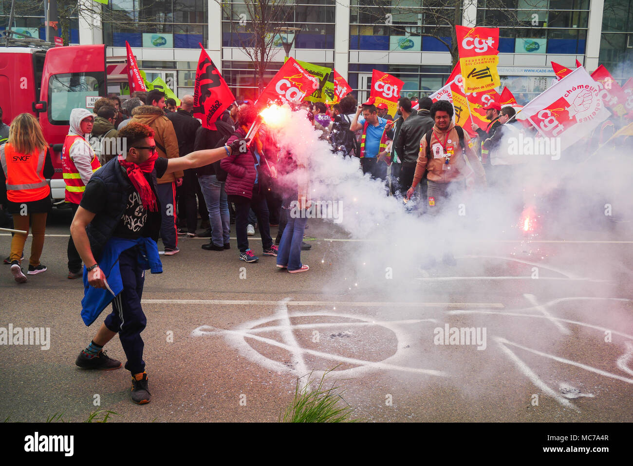 Lyon, France, 13th April 2018: Anarchists are seen in Lyon (Central-Eastern France) on April 13, 2018 as they hold flares, in Part-Dieu area during the demo organized by trade unions on the fifth day of action against SNCF employees status reform engaged by French Government.  Credit: Serge Mouraret/Alamy Live News - Stock Image