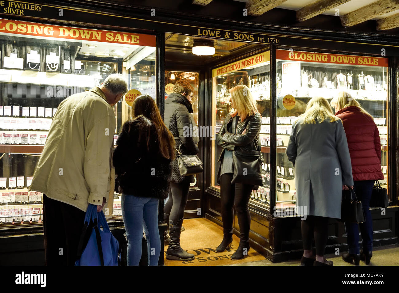 Chester, UK. 13th April 2018. People window shopping at Lowe and Sons jewellery shop on Bridge Street Row. A 50% closing down sale starts at 10am tomorrow, Saturday 14th April. The company has been trading for 248 years and is thought to be the second oldest independent jewellers in the country and the oldest shop still trading in Chester. They have been at their current location since 1804. Credit: Andrew Paterson/Alamy Live News - Stock Image