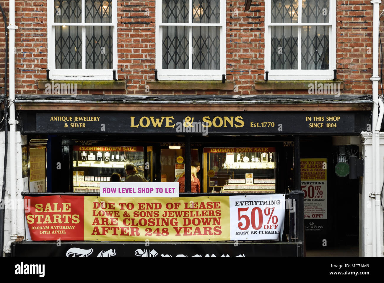 Chester, UK. 13th April 2018. The exterior of Lowe and Sons jewellery shop on Bridge Street Row. A 50% closing down sale starts at 10am tomorrow, Saturday 14th April. The company has been trading for 248 years and is thought to be the second oldest independent jewellers in the country and the oldest shop still trading in Chester. They have been at their current location since 1804. Credit: Andrew Paterson/Alamy Live News - Stock Image