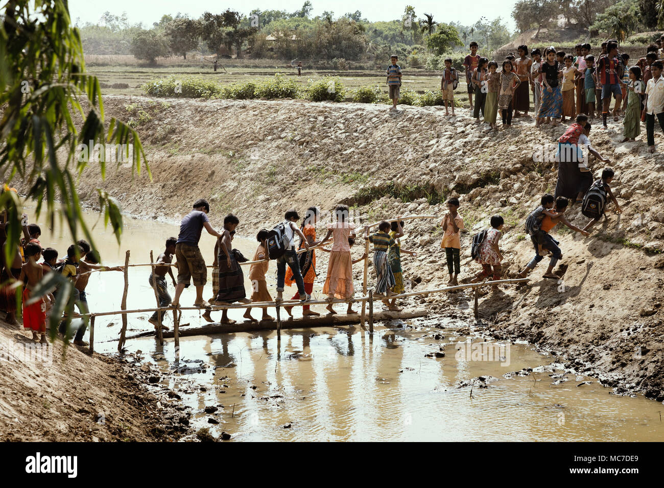 Children cross a makeshift bridge over a stream of sewage into nearby fields to play games. There are now approximately 600,000 Rohingya refugees in the Kutupalong refugee camp of Southern Bangladesh. While preparations are now being made for the Monsoon season which is fast approaching, many NGO's have left leaving much work to be done to make up for their shortfall. - Stock Image