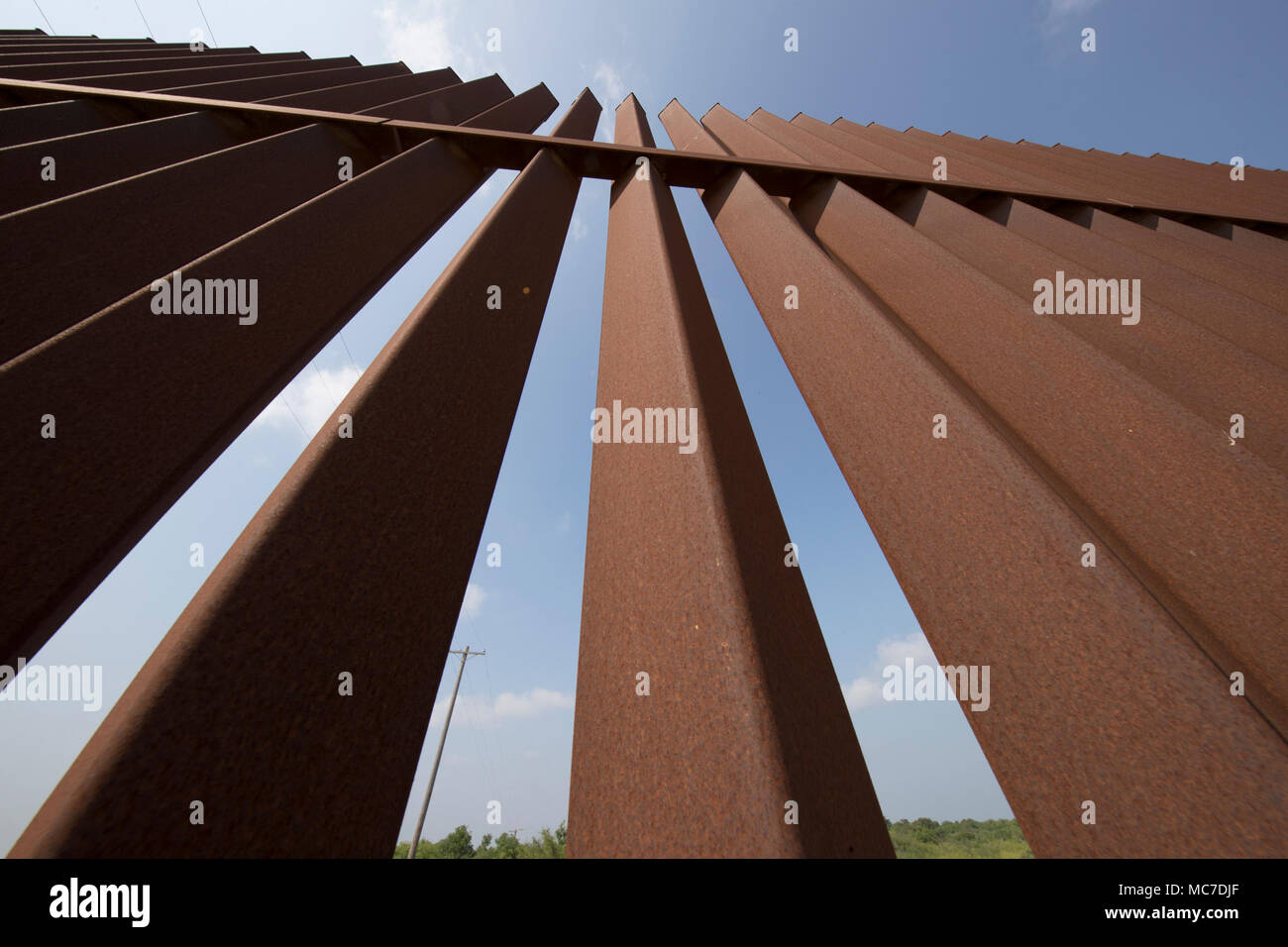 A section of the security fence between the United States and Mexico sits atop a levee of the Rio Grande River on the Texas side of the international border in Hidalgo County. Stock Photo