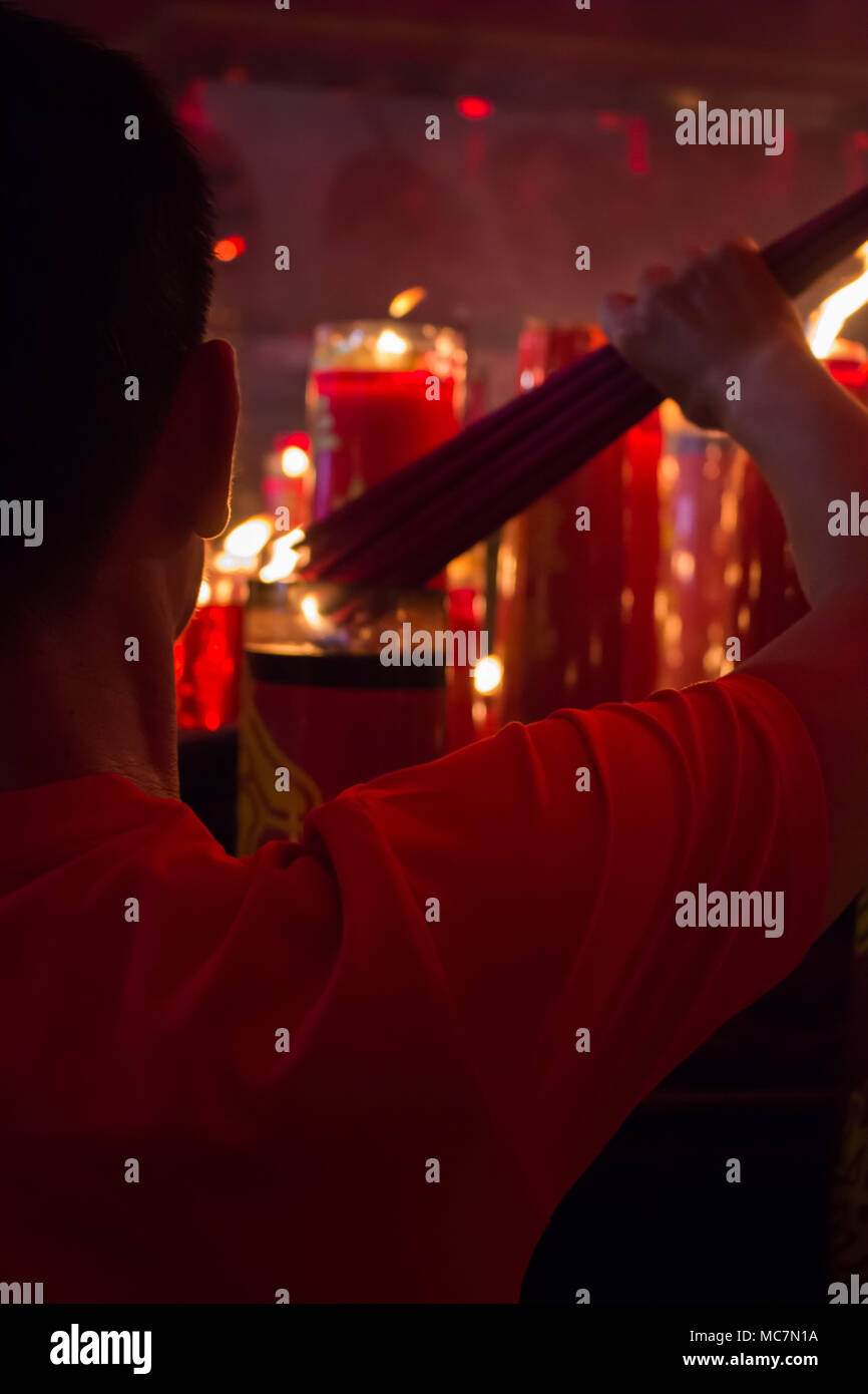 someone who is worshiping in a monastery located in Indonesia to celebrate chinese day / imlek gong xi he was blaming the incense using the fire from - Stock Image