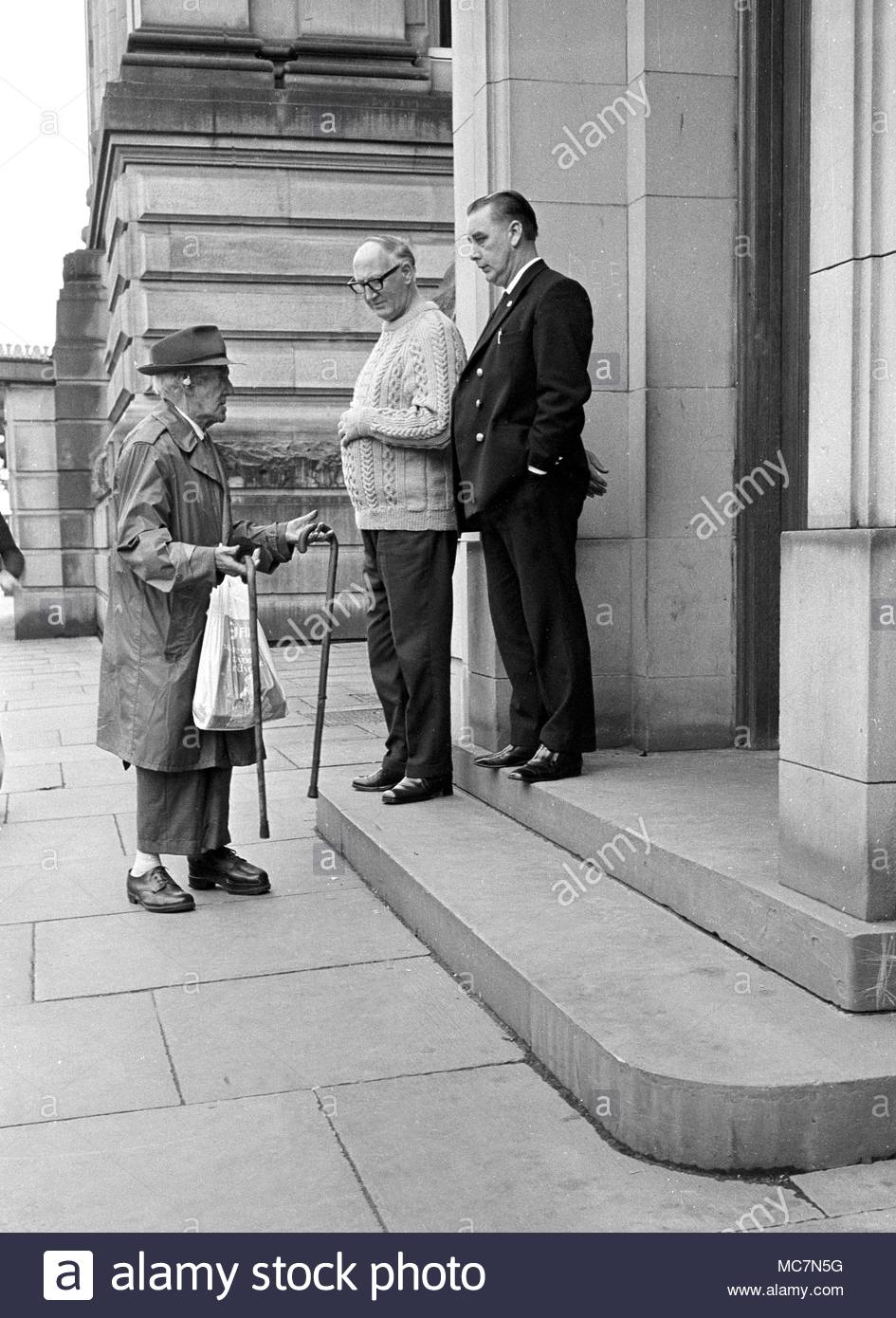 Elderly disabled male talking to staff at one of the side entrances to Bolton Town Hall in the 1970s. The old man has disabilities,  a club foot uses two walking sticks and wears an earing aid photo DON TONGE Photographer - Stock Image