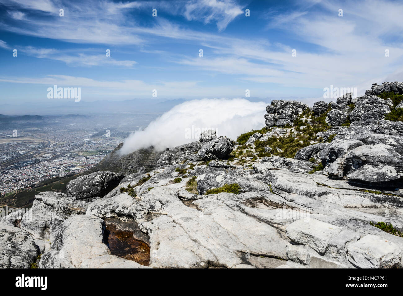 The suburbs of Cape Town below Devil's Peak covered in low cloud seen from the top of Table Mountain, Cape Town, South Africa - Stock Image